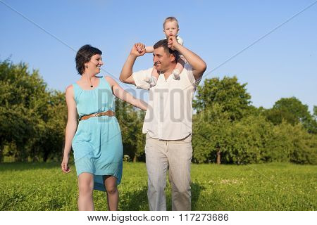 Relationships Concepts. Young Caucasian Family Of Three People Having Good Time Together Outdoors