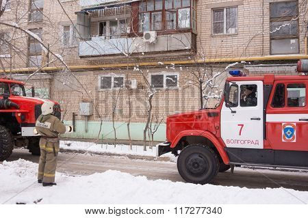 Firefighter Looking At An Apartment Building, Near A Fire Service, There Are Two Machines