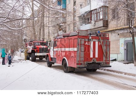 Two Fire Service Cars Are In The Yard Of A Block Of Flats