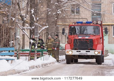 Fire Brigade Are At The Entrance Of An Apartment Building, Standing Next To A Fire Service Vehicle