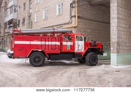Fire Service Car Leaves From The Yard Of A Multistory Building After The Call
