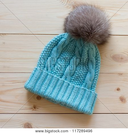 Blue Cap Wool Connected Manually With A Fur Pompon Of Arctic Fox On A Natural Wooden Background