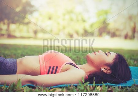 Young Asian woman in sport clothes sleeping on mat in the outdoor park