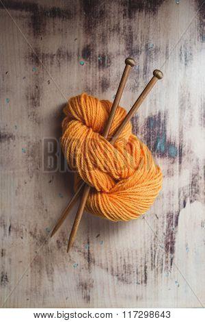 Skein of orange yarn with knitting needles