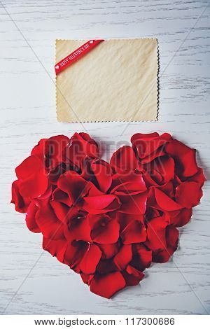 Heart made of rose petals with blank card on wooden background