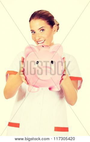 Young beautiful female doctor or nurse holding a piggybank
