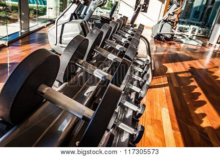 Gym interior with equipment. Dumbbells in the gym.
