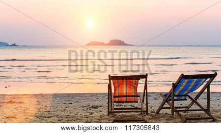 Loungers at the seaside at sunset. poster