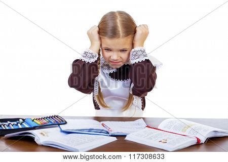 Sad schoolgirl sits at a school desk, isolated on a white background