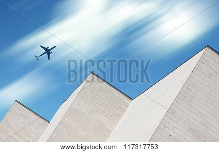 Airplane Flying Over Modern Building