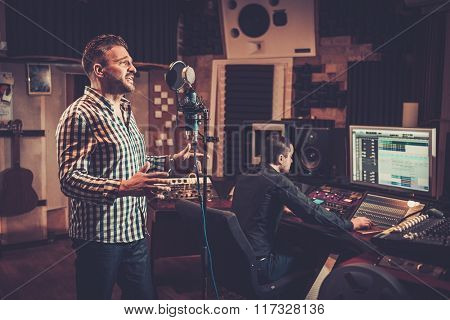 Handsome singer and sound engineer recording a song in the boutique recording studio.