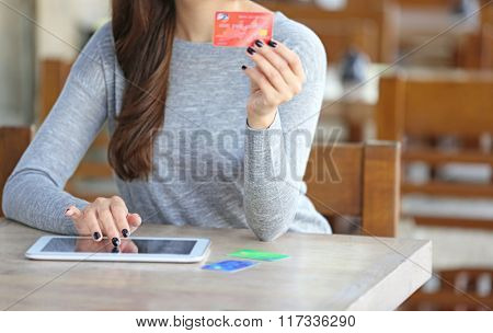 Young woman trying to use bank card for paying bills online