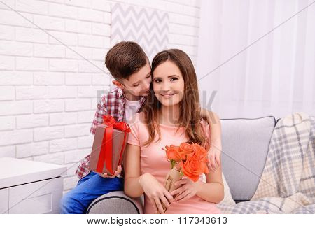 Son celebrating his mother with roses and gift box