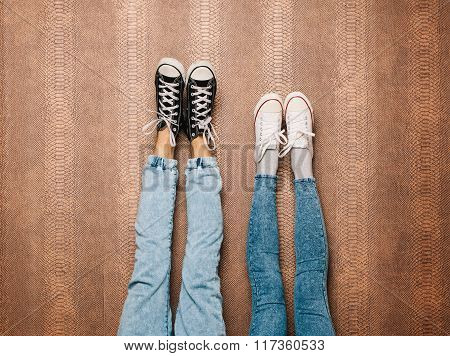 Young fashion couple's legs in jeans and sneakers feet up on the wall. Indoor. Warm color