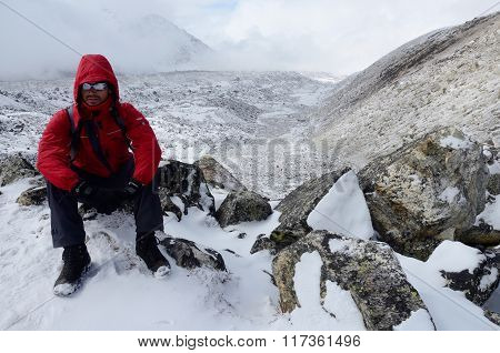 backpacker dressed in red coat and polarizing spectacles resting on his way to Everest Base camp