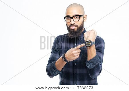 Hairless attractive african young man in glasses with beard pointing on watch