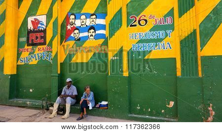Unidentified Cuban male and female sitting underneath colorful revolution Mural in Havana, Cuba.