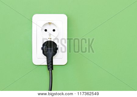 European White Electrical Outlet Socket And Black Cable Pluged In On Green Wall