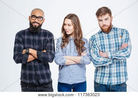 Two young bearded confident men and one pretty young woman standing with arms crossed