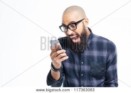Shocked young african american baldheaded man with beard using mobile phone and shouting