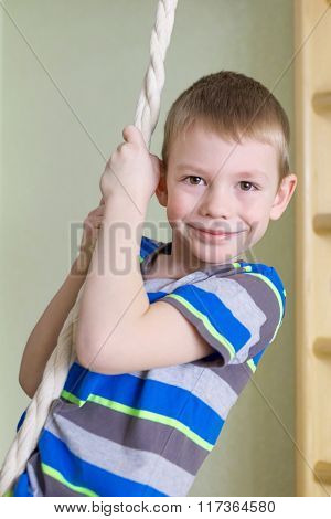 Boy Playing Sports On Rope In Gym Class