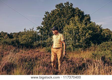 Active Retired Man Walking In Heathland.