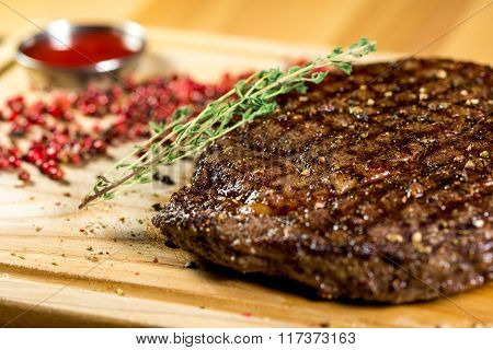 Juicy, And Beautiful Steak With Spiced On The Wooden Background With The Sauce