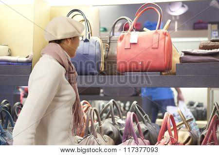 Shopping woman chooses lady's handbag in store. Woman looking to lady's handbag or shop window.