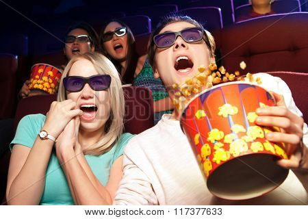 Young couple sitting at the cinema, watching a horrors film. Cinema photo series