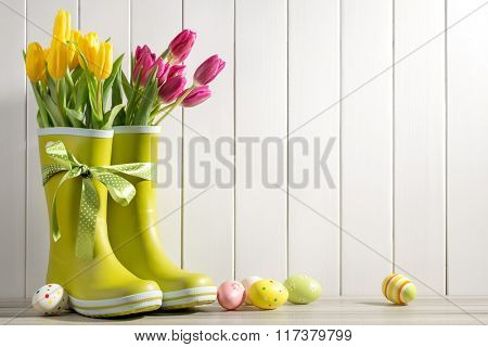 Rain boots, fresh tulips and easter eggs on wood background