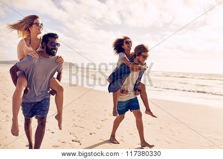 Couples Piggybacking On Sea Shore