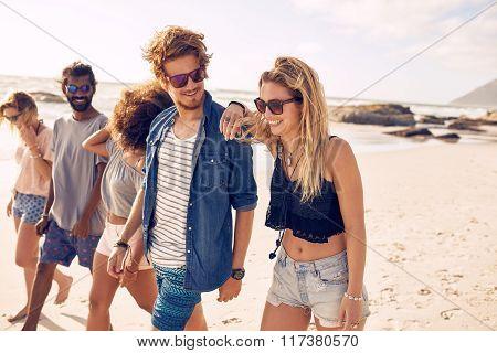 Happy Friends Having A Walk On The Beach