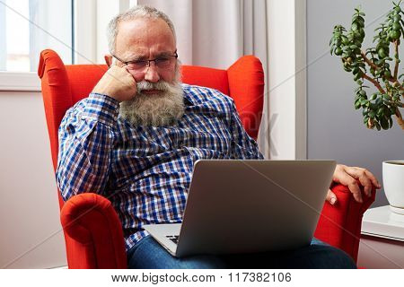 bearded senior man in glasses sitting on the red chair and looking at laptop