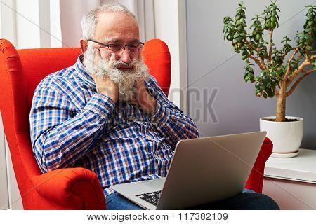 bearded senior man looking at laptop and boring at home