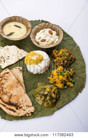 typical maharashtrian food served in plate and bowls made of leaf includes kadhi and shrikhand, plai