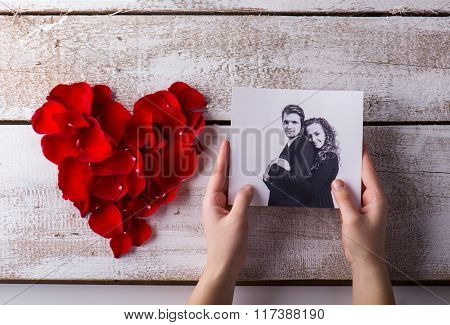 Man holding his and his girlfriends photo. Rose petal heart.