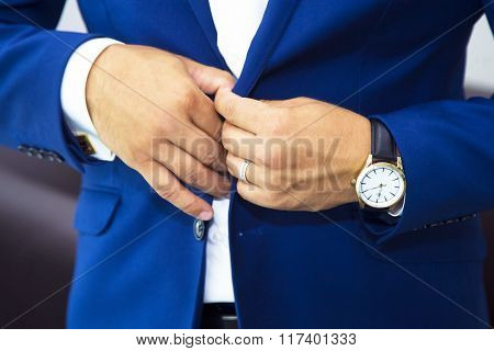groom putting on cuff-links as he gets dressed in formal wear