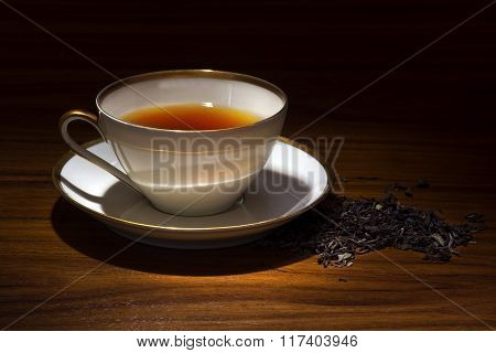 Porcelain Cup With Tea And Some Loose Tea On A Wooden Table