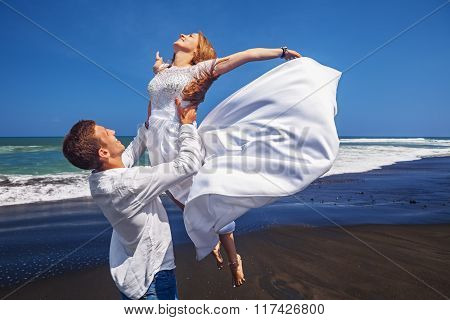 Young Loving Couple Have A Fun On Sea Black Sand Beach