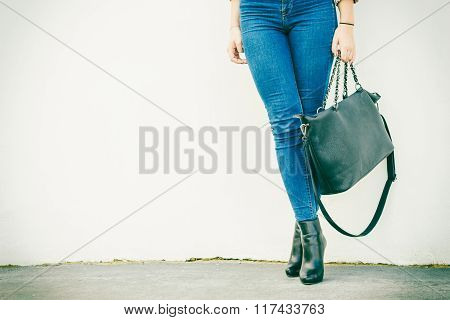 Autumn fashion outfit. Fashionable woman long legs in denim pants black stylish high heels shoes and handbag outdoor on city street poster