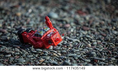 Knocked over by a rogue wave the red robot is down but not defeated. A vintage tin toy laying on a rocky beach after being hit by an ocean wave.