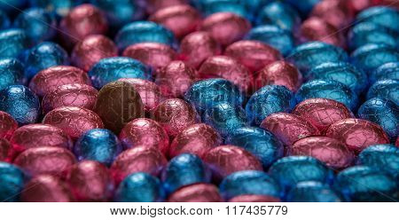 Chocolate Easter Eggs Surrounding One Unwrapped Standing Egg