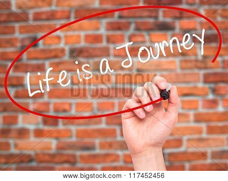 Man Hand Writing Life Is A Journey With Black Marker On Visual Screen.