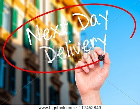 Man Hand Writing Next Day Delivery With Black Marker On Visual Screen.
