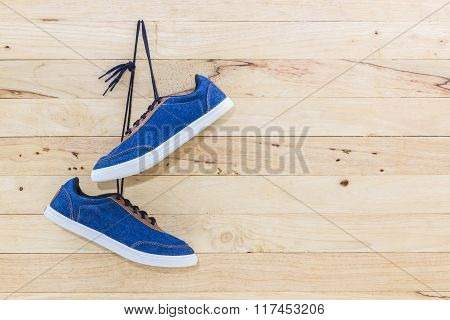 Blue Sneakers Hang On A Nail On A Brown Wooden Wall.