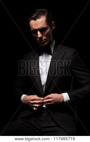 portrait of classy businessman in black suit with bowtie posing seated in dark studio background while closing his jacket and looking down