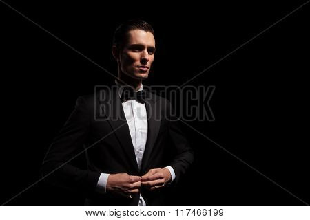 portrait of attractive model in black tux with bowtie posing looking away while closing jacket in dark studio background