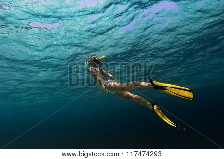 Lady swimming underwater in a tropical sea