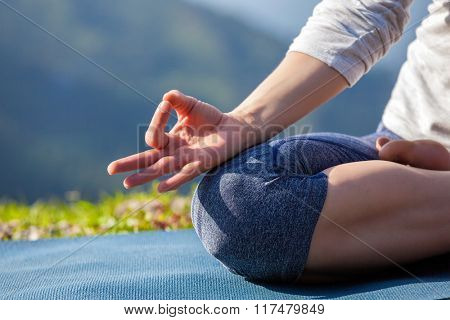 Close up of woman in Padmasana yoga lotus pose with chin mudra outdoors with copyspace