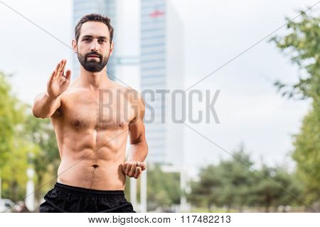 Mann practicing qigong outdoors, office building in background